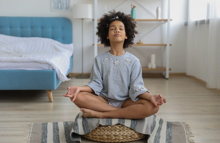 Young girl meditating. These 5 apps teach beginners how to meditate.